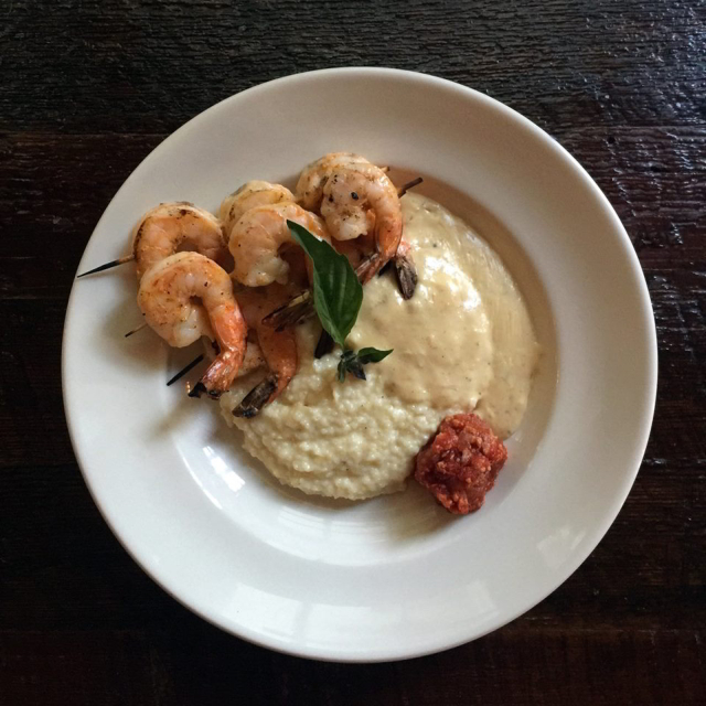 The Sambal Shrimp & Grits at Latitude 29 features spicy grilled shrimp, creamy white pork gravy and bacon marmalade.